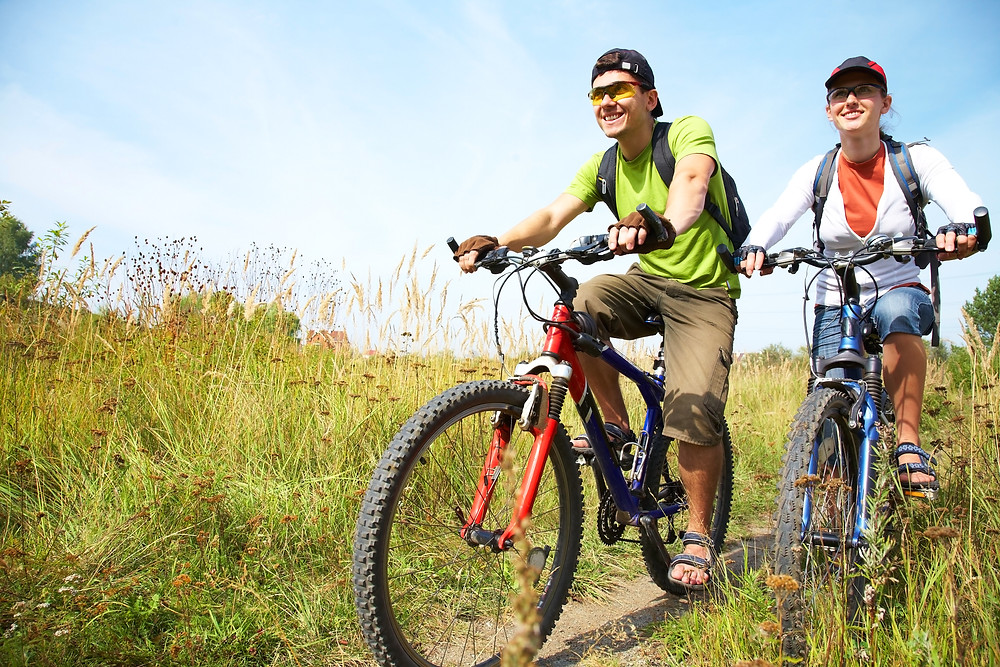 A teen boy and girl riding mountain bikes on a path smiling. Represents the need for depression counseling katy, tx and neurofeedback for depression katy, tx 77494.