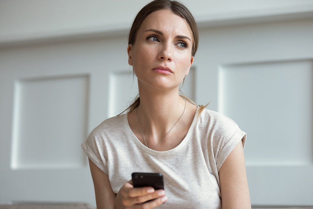Woman holding a phone looking pensive. Represents family counseling katy tx and Houston. Also represents neurofeedback for anxiety in Katy, Texas and PTSD treatment houston texas.