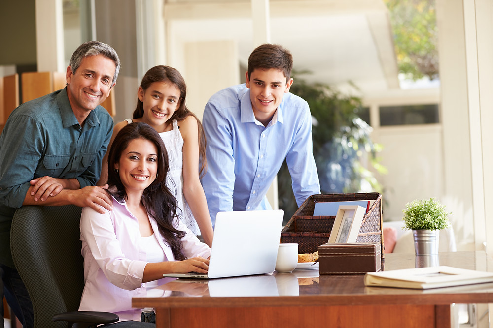 Hispanic family together at a desk with a laptop. Represents outcome of family therapy for gifted teens katy, tx and teen counseling in Katy, Tx and Houston, Tx.