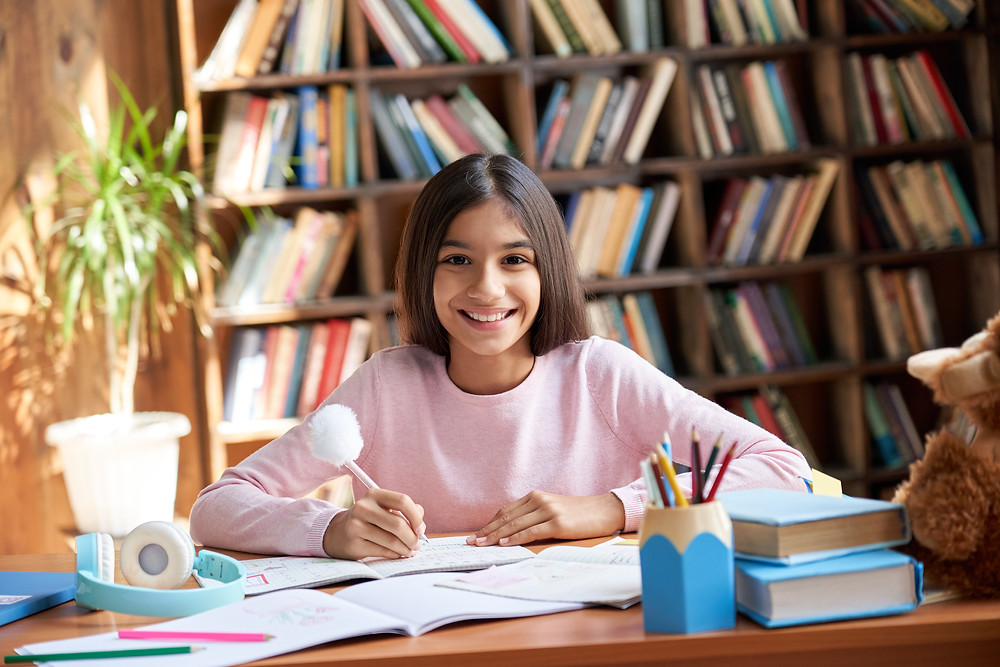 Hispanic teen girl doing homework at her desk. This represents the need for teen treatment for shame houston, tx and teen anxiety therapist houston, tx. This also represents the need for trauma therapy for teens houston, tx and therapy for teen depression in houston, tx.