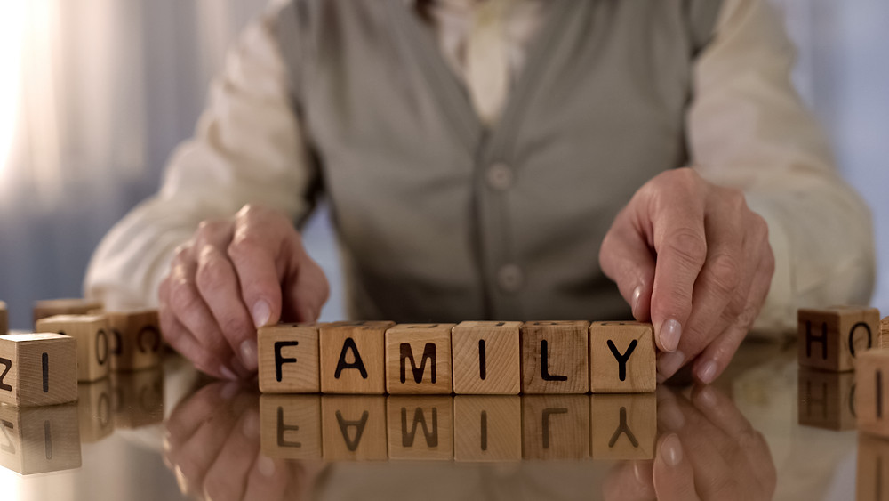 Man spelling family with block letters. Represents family therapy in katy, tx. Also represents family counseling katy, tx and family counseling 77494.