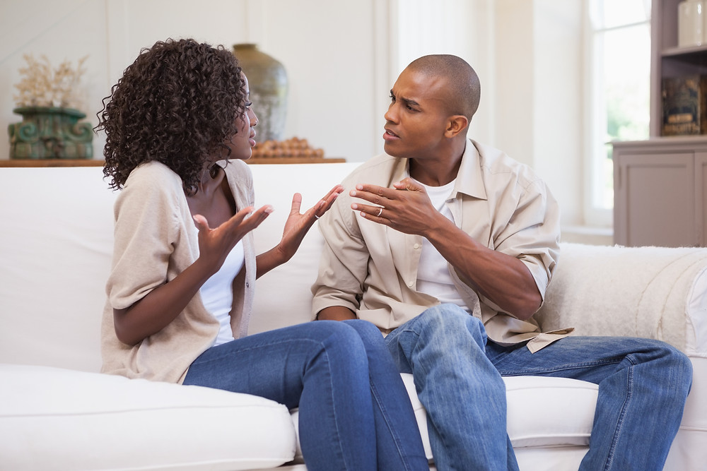 Black couple arguing on the couch. Represents the need for marriage counseling katy, tx 77494. Also represents the need for couples therapy katy, tx 77494.