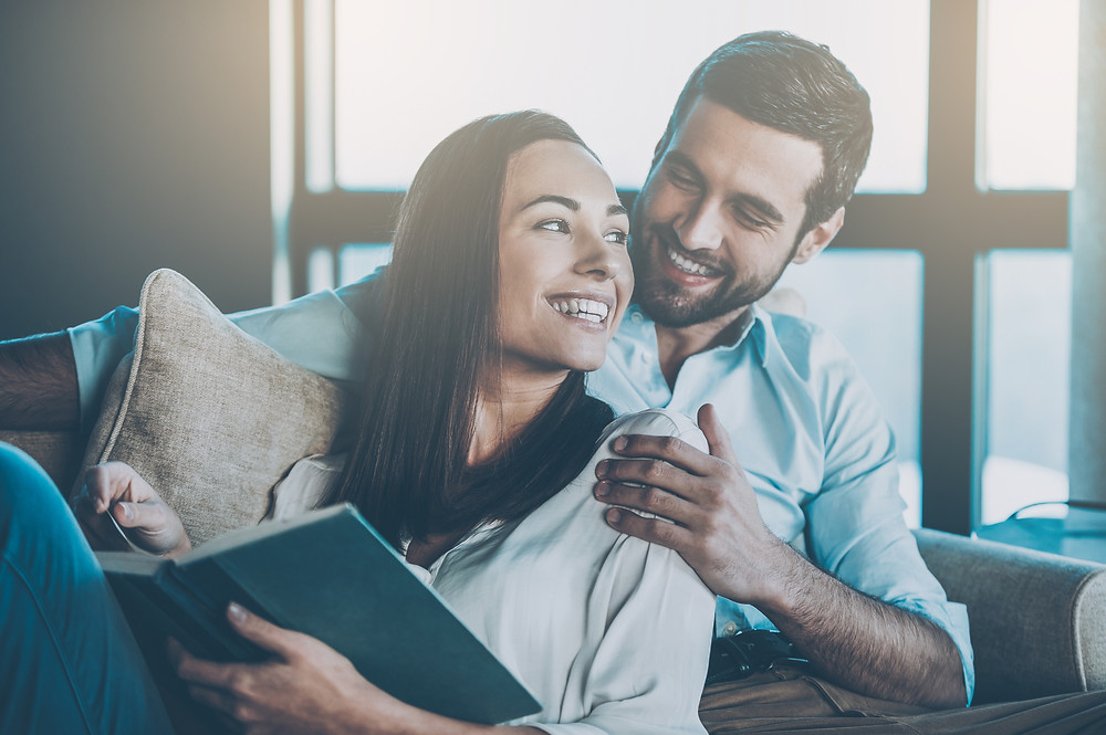 Woman leaning against a man sitting on the couch reading. Represents the need for couples therapy katy, tx 77494.  Also represents the need for marriage therapy and marriage counseling katy, tx 77494.