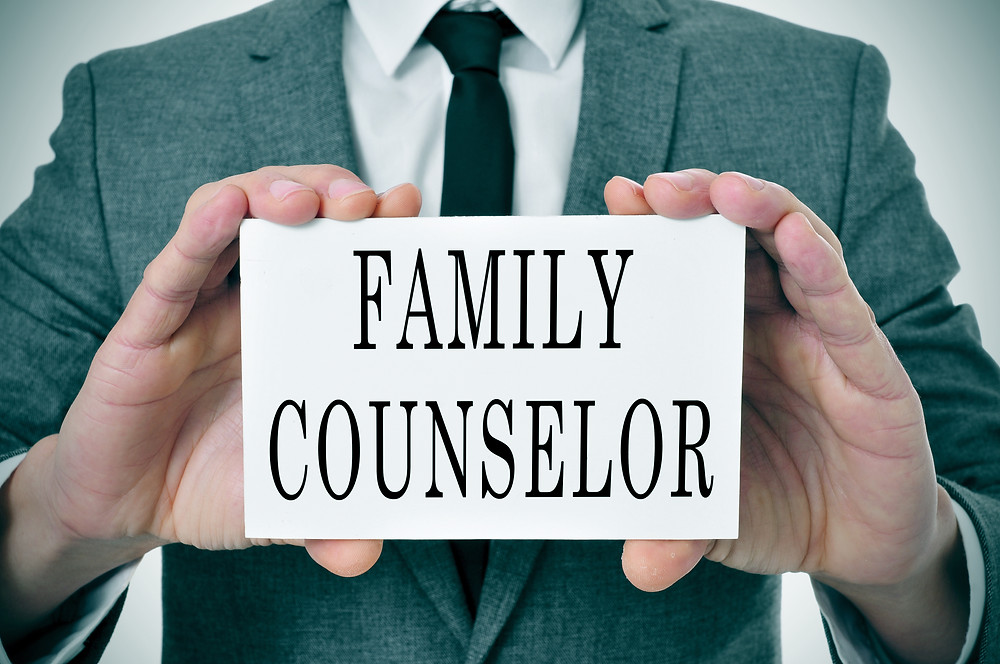 Man in suit hold card saying Family Counselor. Represents the need for family counseling katy tx 77494. Also represents the need for family therapy houston tx and neurofeedback for anxiety katy texas 77494.