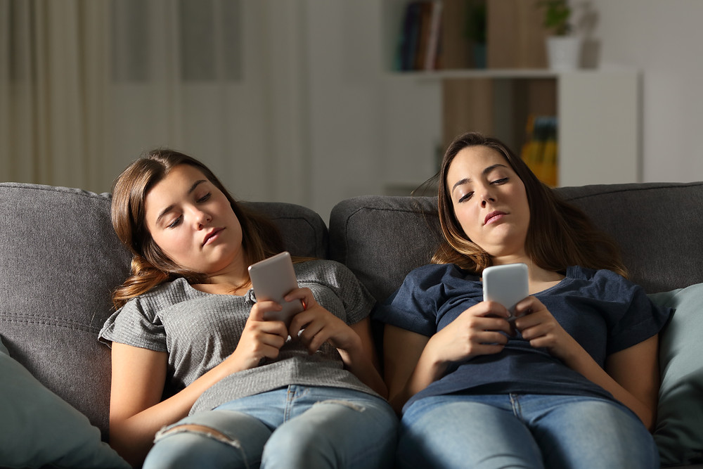 Two girl friends on a couch looking at their phones. Represents the need for neurofeedback for anxiety houston texas. Also represents the need for neurofeedback for anxiety katy texas 77494.