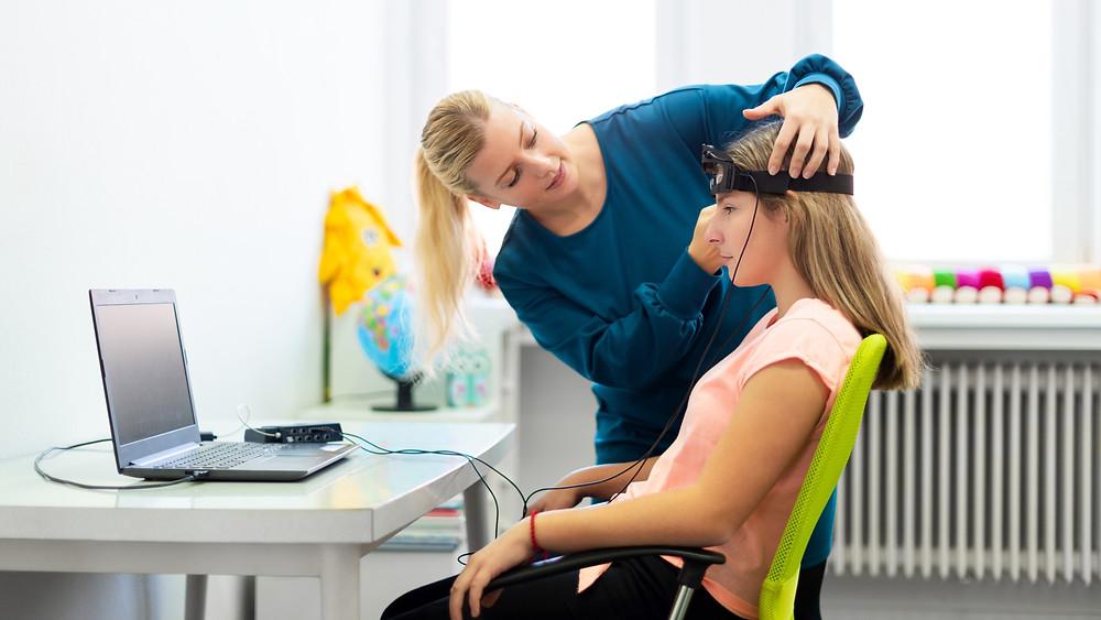 Woman putting neurofeedback on a teen girl. Represents neurofeedback for ADHD Houston Texas. Also represents neurofeedback for anxiety katy texas 77494.
