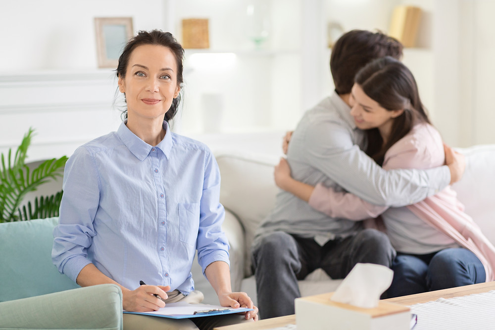 Woman holding clip board smiling with father and daughter hugging in background. Represents family counseling and family counseling in katy, tx. Also represents family therapy in katy, tx 77494.