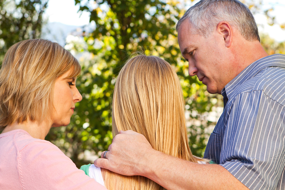 Parents comforting their teen girl outdoors. Represents teen experiencing teen trauma teen anxiety who needs counseling katy tx 77494.