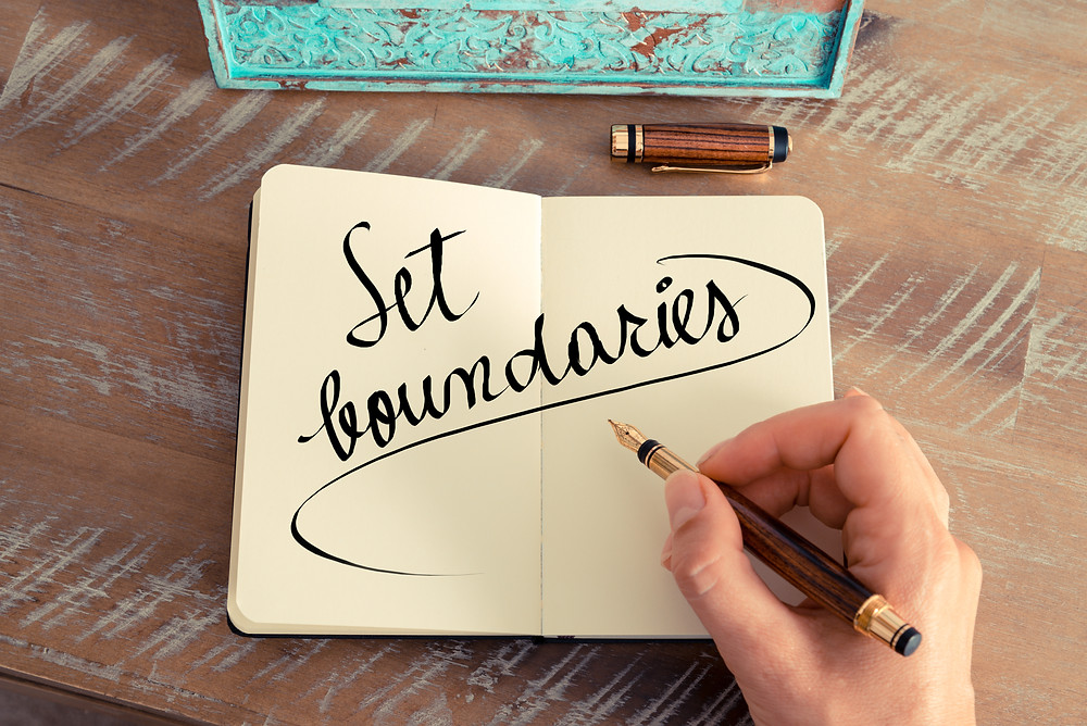"""Hand holding a pen with """"set boundaries"""" written. Represents the need  for counselors specializing in trauma katy, tx. Also represents the need for neurofeedback for adhd houston texas."""