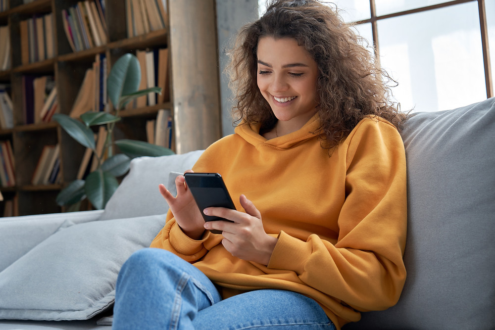 Girl sitting on couch looking at phone smiling. Represents the need for therapists for young adults katy, tx 77494 and young adult counseling katy, tx 77494.