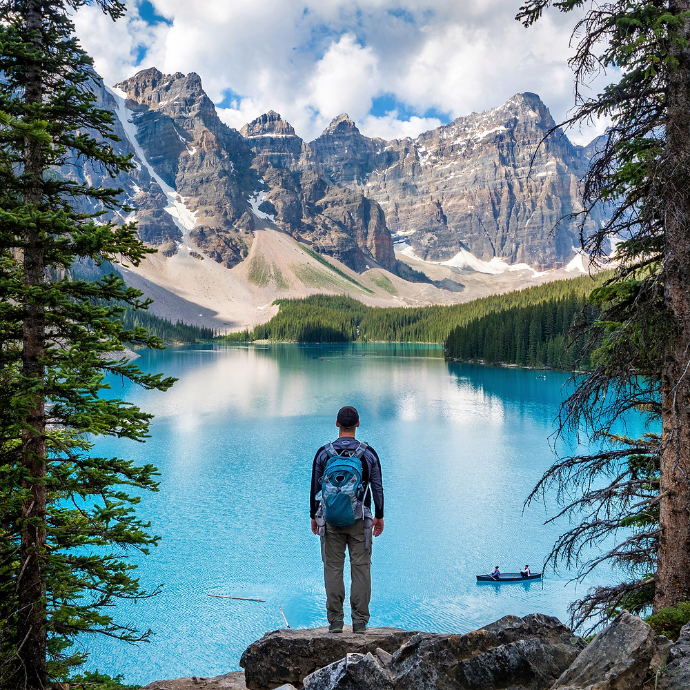 Man with backpack on standing in front of a lake and mountains. Represents the need for therapists for young adults katy, tx 77494.  Also represents the need for young adult therapy katy, tx 77494 and edmr in katy, tx 77494.