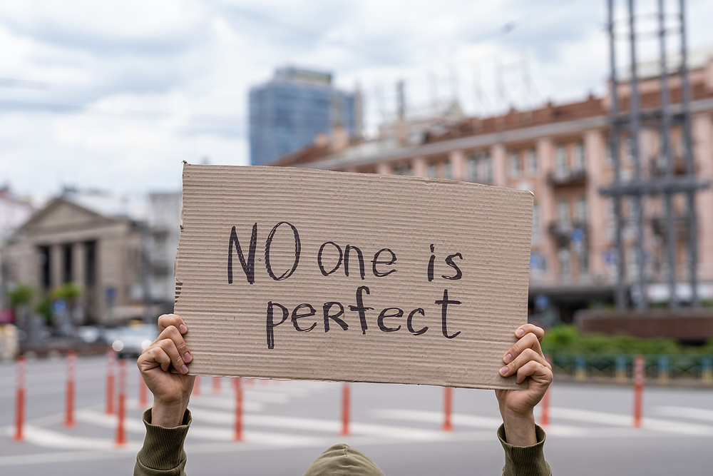 "Holding a sign above his head reading, ""no one is perfect"". Represents parents raising teens and need for teen counseling katy, tx and counseling for families in katy and houston. Also represents teen anxiety counseling, katy tx 77494."