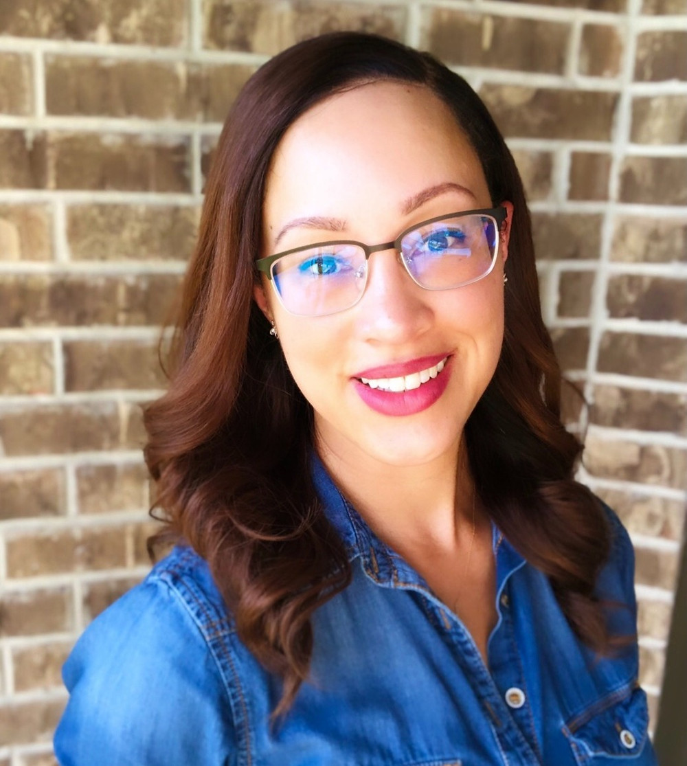 Picture of woman standing in front of brown brick wall, glasses, button up denim shirt smiling. She is a young adult therapist in katy, tx and a young adult counselor in katy, tx 77494. She provides therapy for young adults katy, tx and counseling for young adults katy, tx 77494.