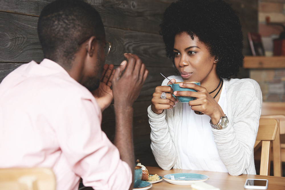 Black woman with afro talking with black man. Represents the need for couples therapy katy, tx 77494. Also represents the need for marriage counseling katy, tx 77494.