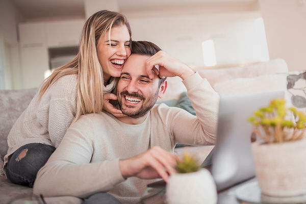 Couple sitting on couseh smiling. Represents the need for marriage counseling katy, tx 77494.  Also represents the need for couples therapy katy, tx 77494.