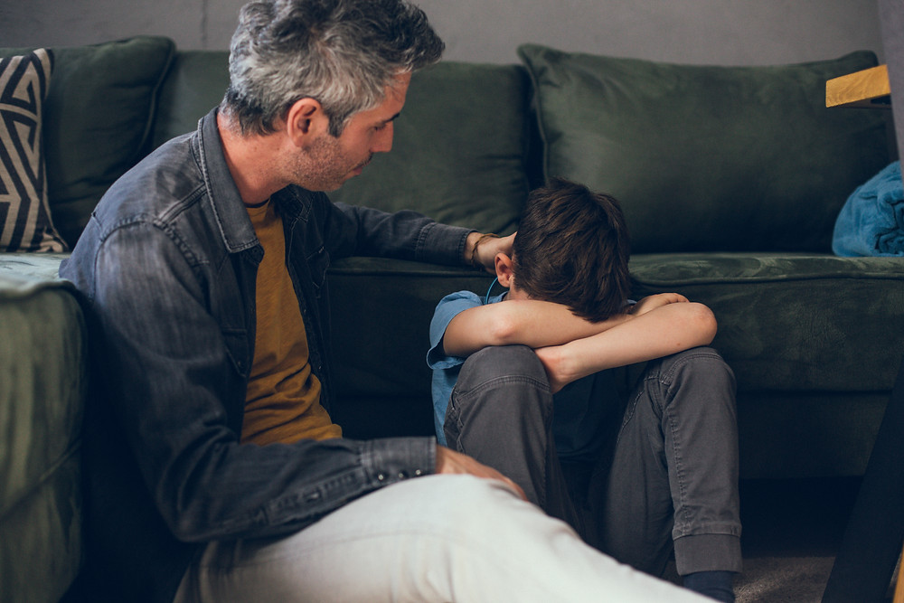 Father trying to comfort his son. Represents need for teen depression therapy in katy, tx and counselor for teen depression in katy, tx. Also represents family counseling and counseling for families 77494.