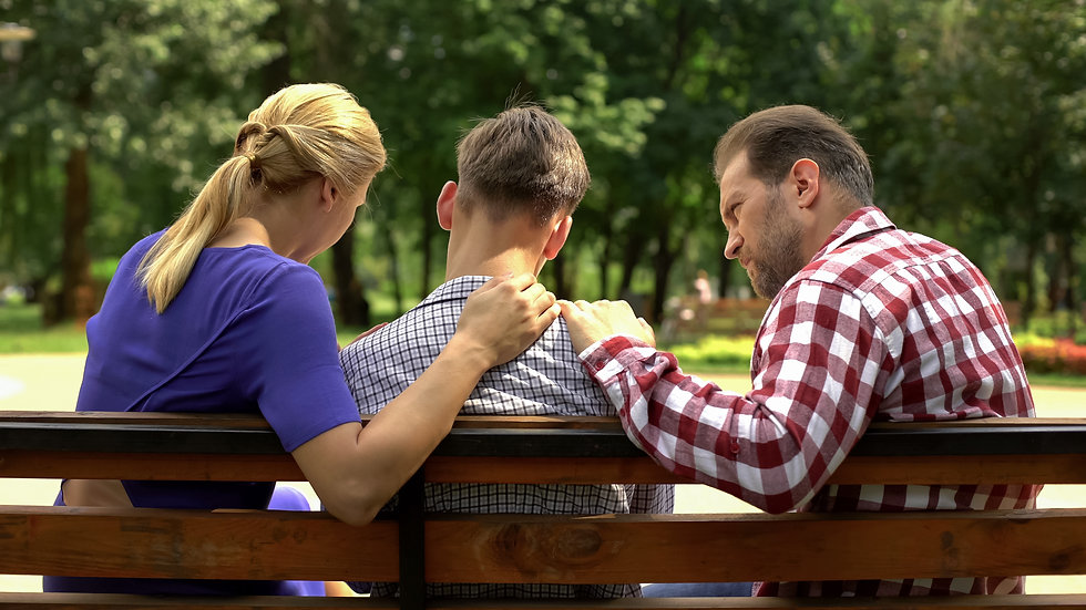 Parents comforting teen son on a park bench. Represents need for teen depression counseling and need for a therapist for teen depression in katy texas and houston texas. 77493.