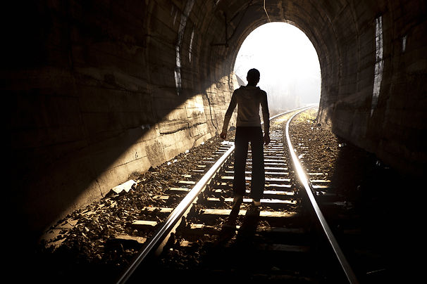 Teenager in dark tunnel walking towards the light. Represents hope in ptsd counseling for teens katy texas. Hope for teenagers in ptsd counseling for teens in houston texas. 77493.