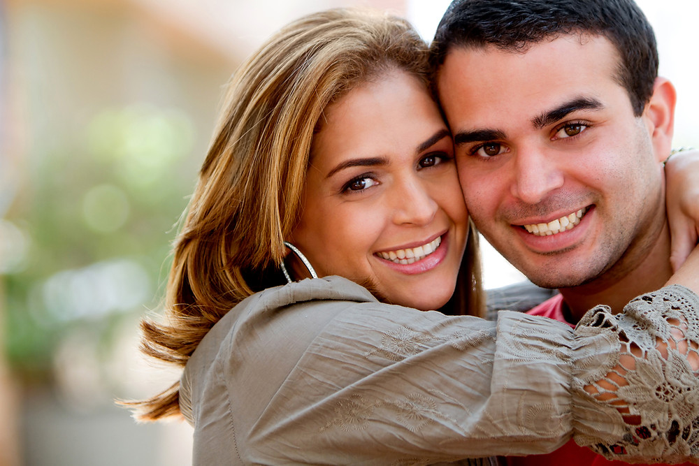 Hispanic couple hugging, smiling, looking at the camera. Represents the need for marriage counseling katy, tx and couples therapy katy, tx 77494.