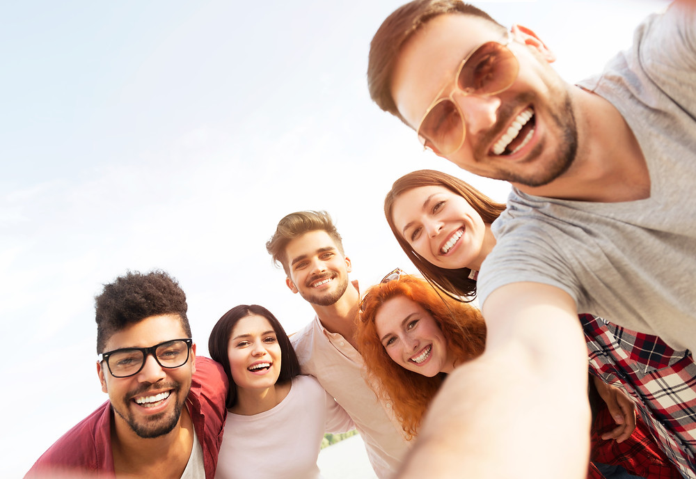 Young adult men and women taking a group selfie smiling. This represents the need for young adult therapist katy, tx and young adult counseling katy, tx 77494.