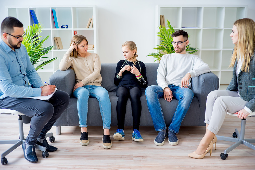 A counselor providing therapy for a family who is sitting on a couch with mom on a chair. This represents teen counseling in katy, tx 77494 and family counseling. This also represents counseling for teens in houston texas.