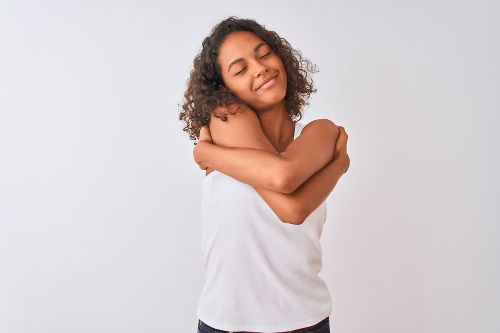 Black girl hugging herself. This represents trauma treatment in katy, tx and neurofeedback for PTSD katy texas. Also represents EMDR for teens in katy tx.