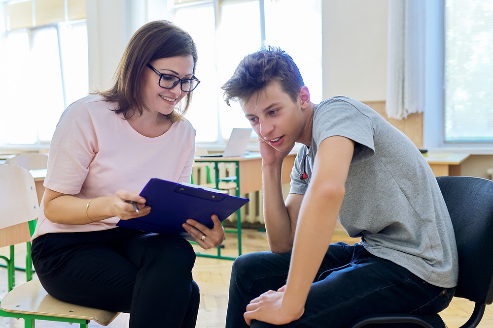 Teen boy and woman with a clip board sitting on chairs talking. Represents the need for counseling for teen depression in houston tx. Also represents the need for therapy for teen depression in houston, tx.