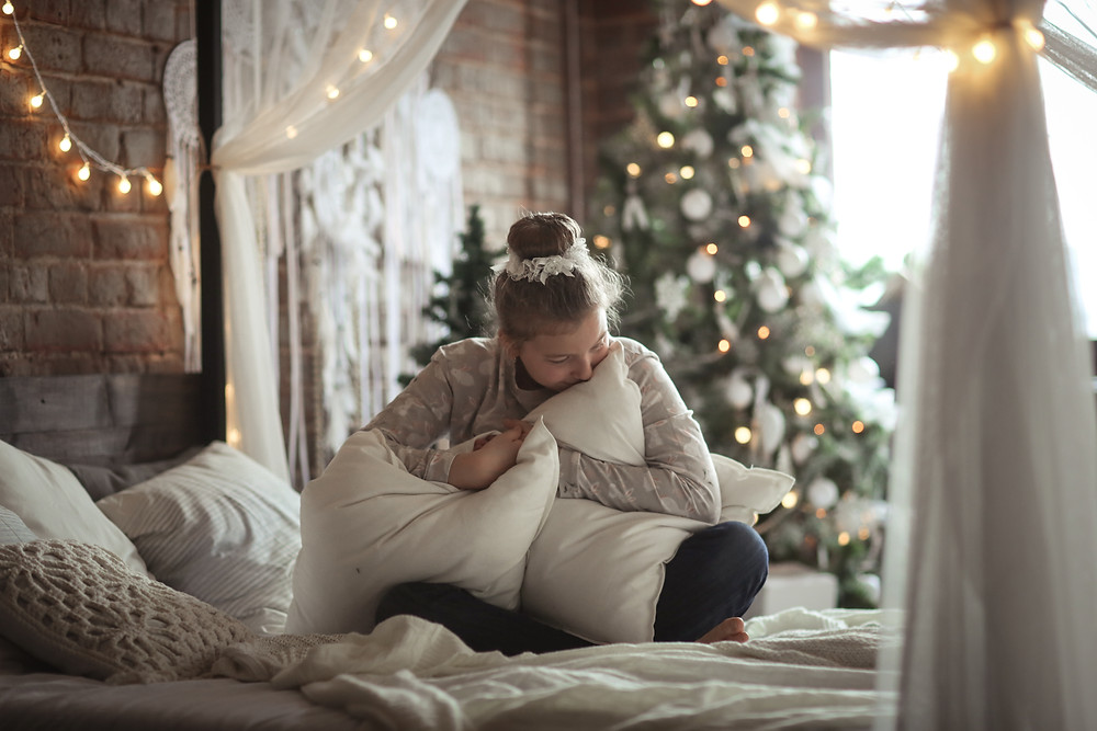 Sad girl hugging pillows on bed Christmas tree in background. Represents need for family therapy in katy tx 77494. Also represents need for counseling for teens and counseling for teen depression in katy, tx. .