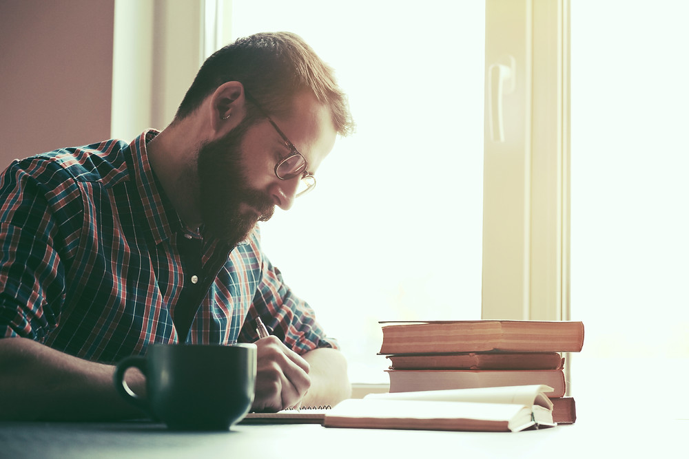 Man in flannel shirt, glasses, and beard journaling. Represents the need for couples therapy katy, tx 77494. Also represents the need for couples counseling katy, tx and marriage counseling katy, tx 77494.