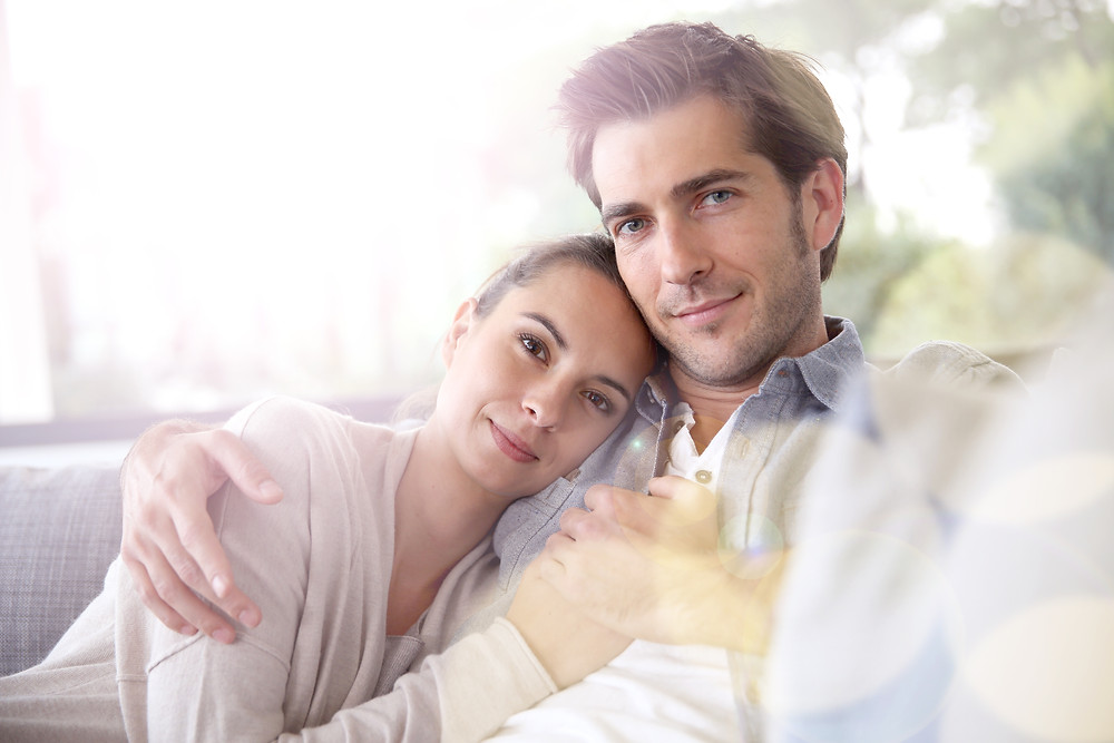 Man and wife holding each other on couch. Represents the need for couples therapists katy, tx 77494.  Also represents the need for marriage counselors katy, tx 77494.