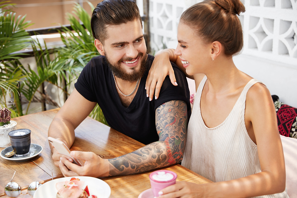 Man and woman sitting at table looking at each other smiling. This represents the need for marriage counseling katy, tx and need for a marriage therapist katy, tx 77494.