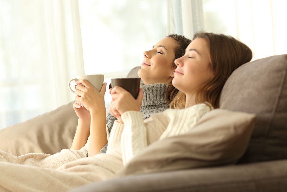 Mother and daughter with mugs relaxing on couch. Represents the need for family therapy and teen anxiety counseling in katy, tx. Also represents the need for trauma therapy katy, tx 77494.