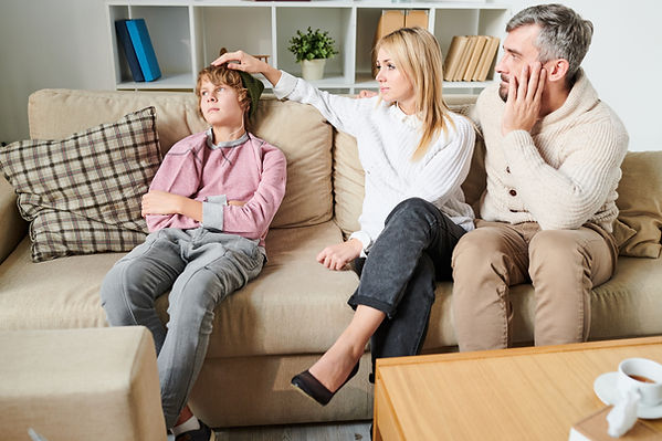 Concerned parents on couch with son. Represents the need for therapy for teen depression in katy texas. May represent need for teen couseling in Houston texas.