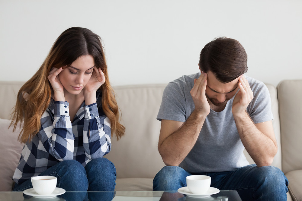 Couples sitting on couch looking down rubbing their temples. Represents the need for marriage counseling katy, tx 77494. Also represents the need for marriage counseling katy, tx 77494.