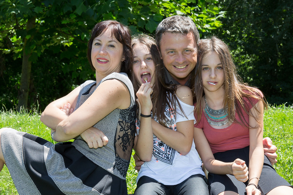 A family with teen girls smiling outside. Represents family therapy & teen therapy for trauma therapy & PTSD treatment katy texas 77493.