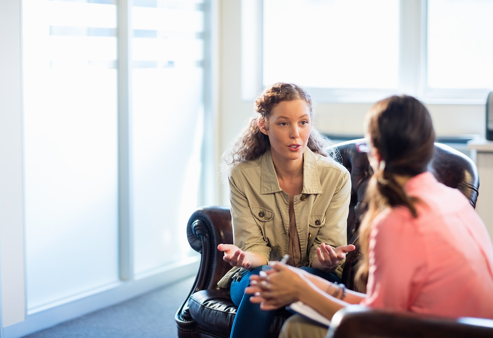 Young woman talking with another woman sitting on leather chairs. Represents the need for young adult counseling katy, tx 77494. Also represents the need for young adult counselors katy, tx 77494.