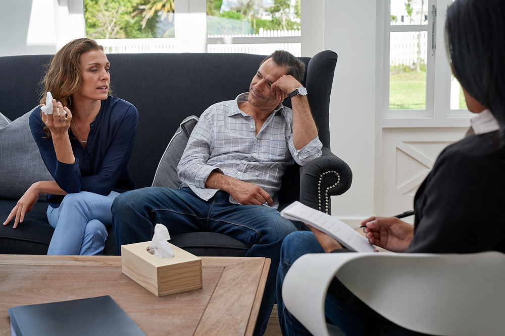Man and woman on couch talking to a lady with a clipboard and pen. Represents the need for marriage counseling katy, tx and couples therapy katy, tx 77494. Also represents the need for marriage therapist katy, tx 77494.