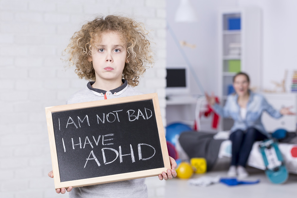 Boy holding up chalk board with I am not bad I have ADHD written. Represents the need for neurofeedback for ADHD katy texas 77494. Also represents the need for neurofeedback for adhd houston texas.