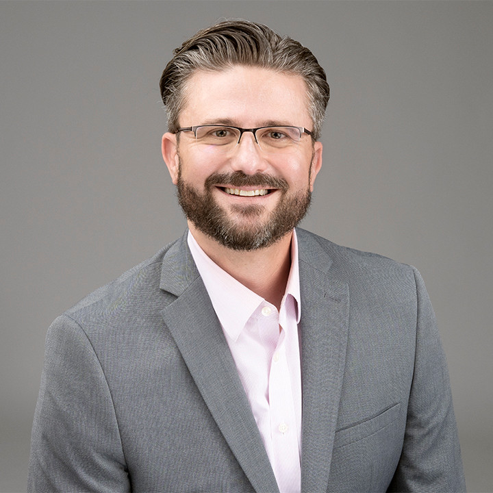 Man in glasses, pink dress shirt, and grey sports coat smiling. He provides family therapy in katy, tx and ptsd counseling katy, tx. He also provides ptsd counseling katy texas 77494.
