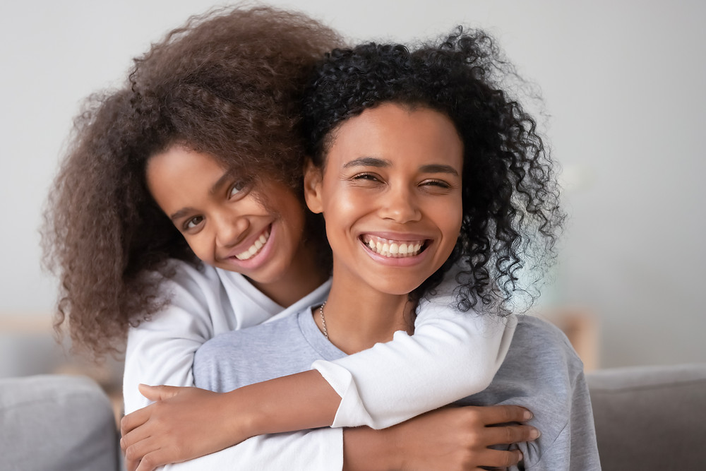 Black daughter with arms around black mother. Represents the need for family counseling and family therapy in katy, tx 77494.  Also represents the need for cognitive behavioral therapy for teens katy, tx 7749.