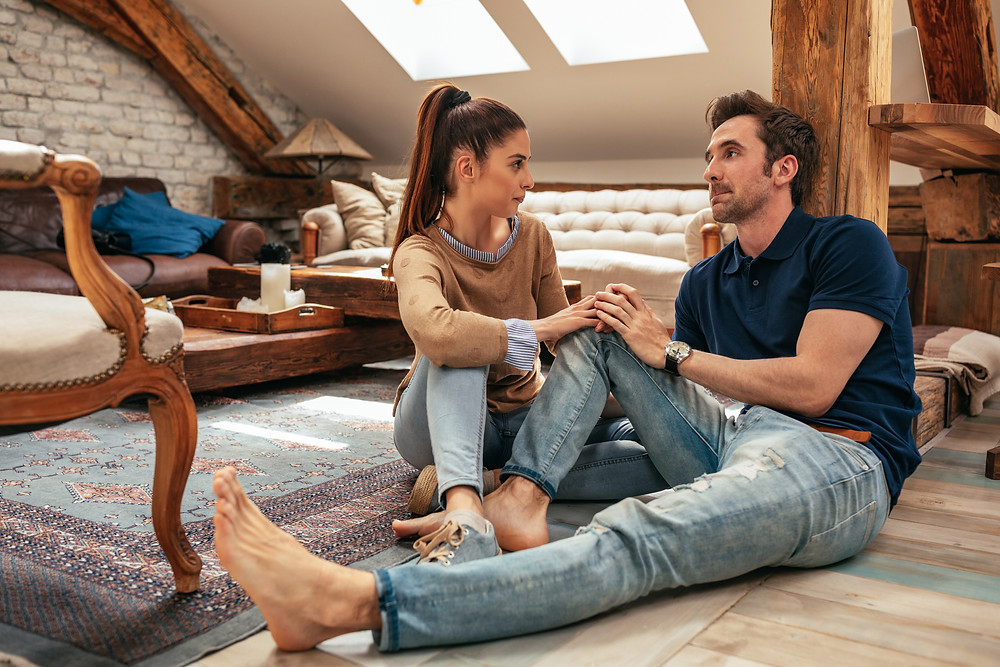 Man and woman sitting on the floor, holding hands, talking. Represents the need for couples therapists in katy, tx 77494. Also represents the need for marriage therapists katy, tx 77494.