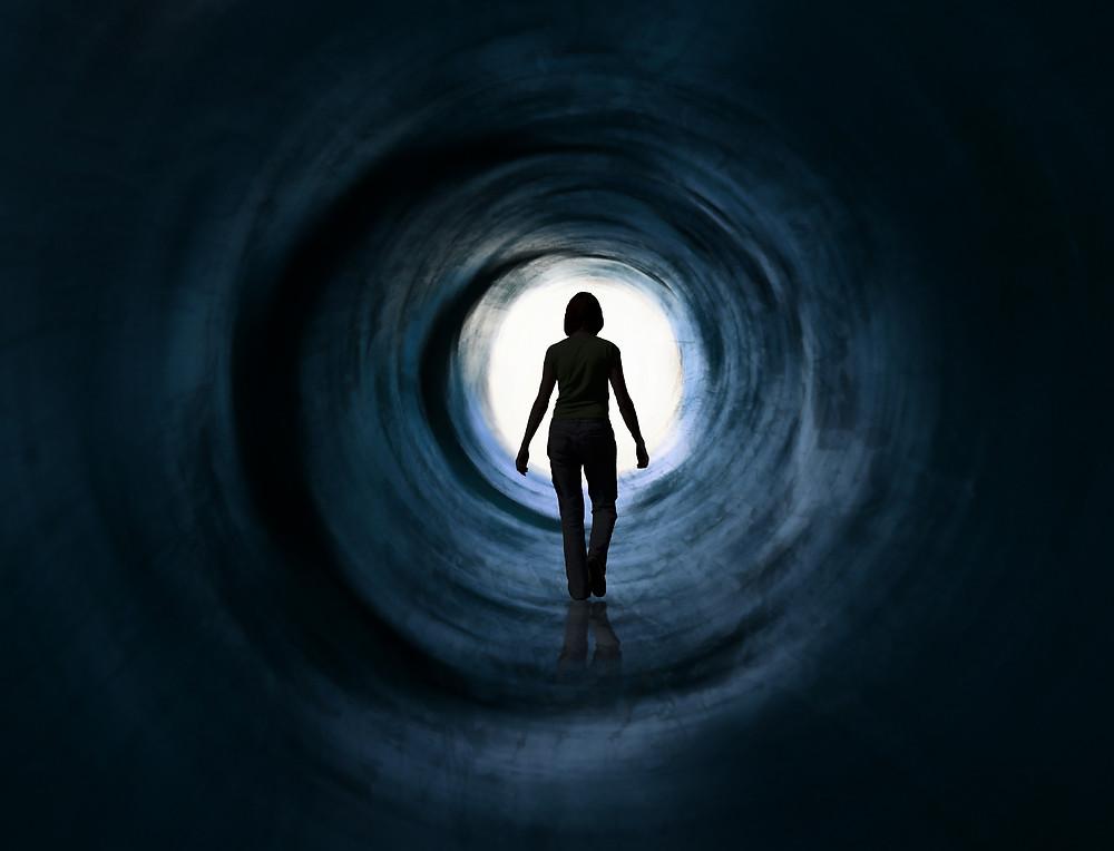Teen walking down tunnel towards light. Represents neurofeedback in katy texas. Also represents depression counseling katy texas 77494.
