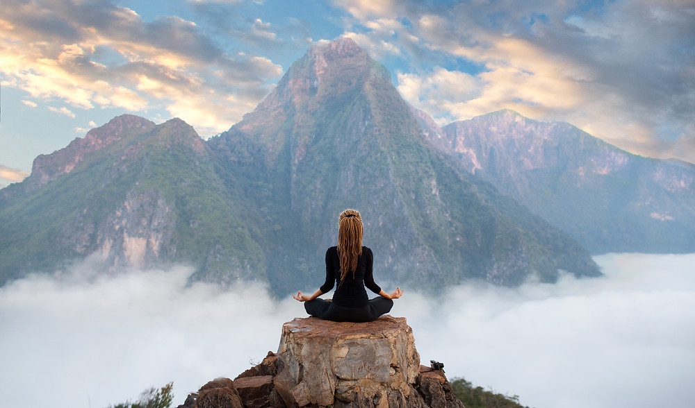 Lady sitting in yoga position in front of mountain with clouds under her. Represents PTSD counseling for teens katy, tx, teen therapy, and family therapy. Also represents teen depression counseling in katy, tx and Houston, tx.