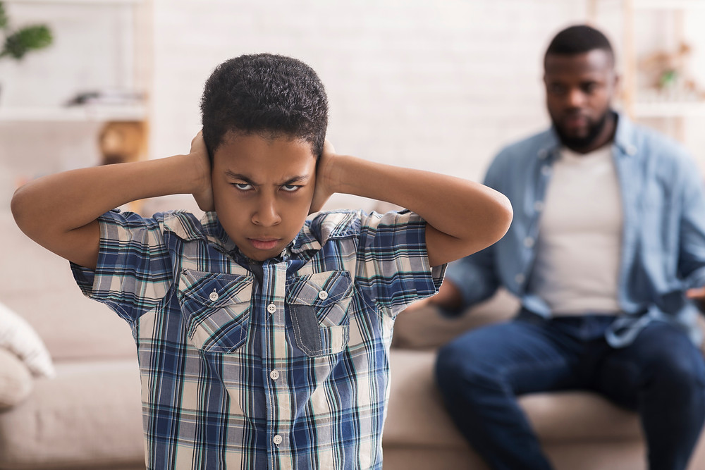 Black father talking, son with hands over his ears. Represents the need for family counseling katy, tx. Also represents the need for depression therapist katy tx 77494.