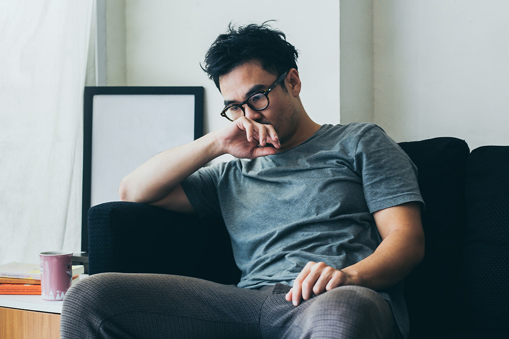Young man in glasses sitting on couch looking worried. Represents the need for counseling for young adults in katy, tx 77494.  Also represents the need for therapists for young adults katy, tx 77494.