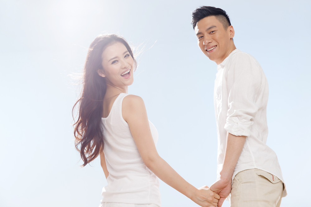 Asian couple holding hands looking back and smiling. Represents the need for couples therapy katy, tx and couples counseling katy, tx 77494. Also represents the need for marriage therapy katy, tx and marriage counseling katy, tx 77494.