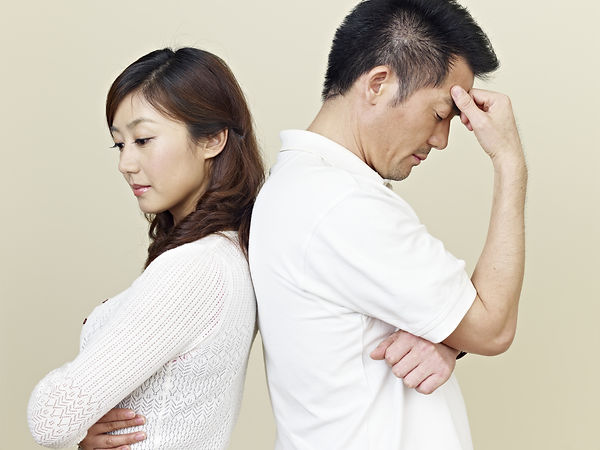 Asian couple leaning back to back looking stressed. Represents the need for marriage counseling katy, tx 77494.  Also represents the need for couples therapy katy, tx 77494.