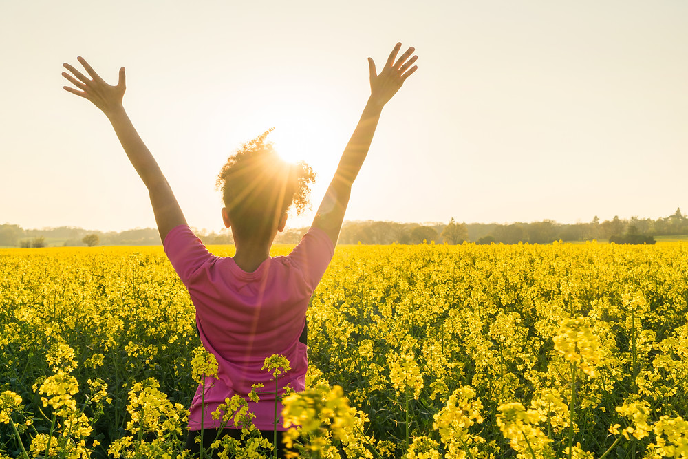 African American girl in flower field raising her arms in the air facing the sun. Represents successful teen counseling houston texas and depression counseling houston texas. Represents teen counseling services katy texas 77494.