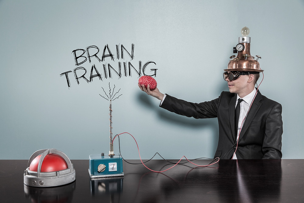 Man with machine on his head, table and holding brain with brain training written on a wall. Represents Neurofeedback counseling and neurofeedback in Houston, Tx. Also represents neurofeedback in katy texas 77494.