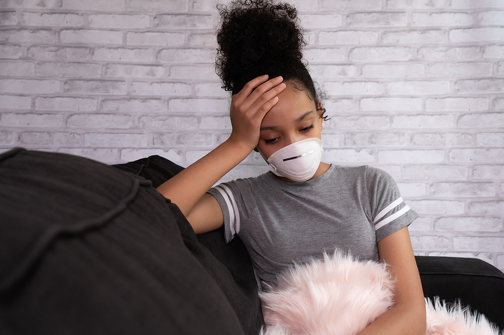 Girl sitting on couch, hand on forehead, wearing a mask over mouth looking sad. Represents the need for counselors specializing in trauma katy, tx and emdr for ptsd katy, tx 77494.